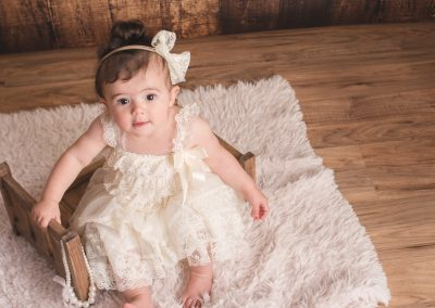 baby girl sitting on wooden bed