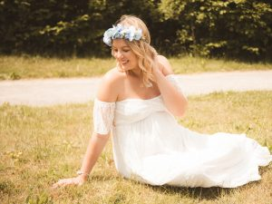 outdoor maternity photo on the grass in a white dress