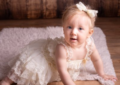 baby girl in white dress and bow looking at camera