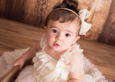 baby girl in white dress sitter session
