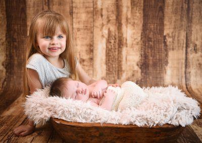 newborn baby in wooden bowl with sister sat next to her