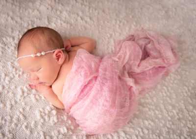 newborn baby girl sleeping draped with pink silk