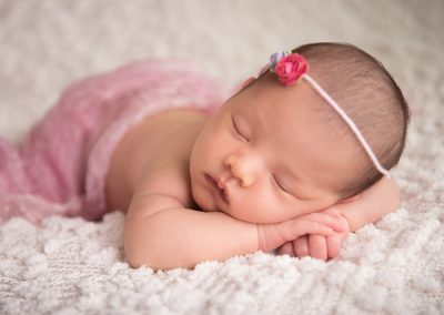 newborn baby girl head on hands with floral headband